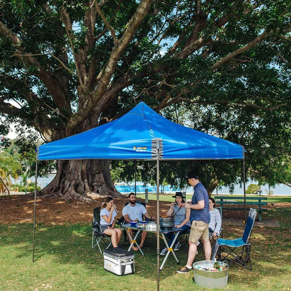 OZtrail Fiesta Deluxe 3.0 Blue Gazebo - Setup outdoors with people dining underneath