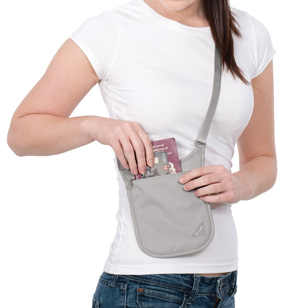 Pacsafe Coversafe V75 RFID Neck Pouch - Woman taking passport and credit card out of pouch