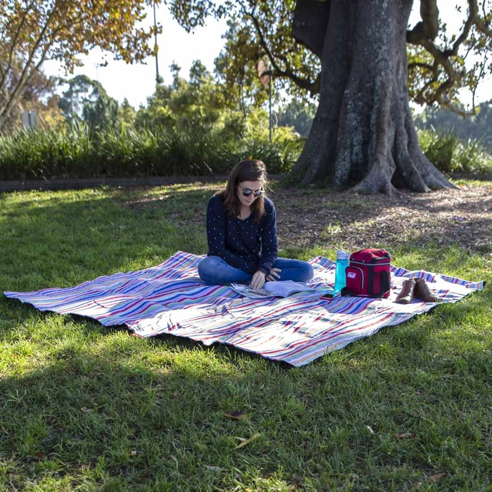 Coleman 9 Can Soft Cooler Bag - Woman sitting next to cooler on a picnic rug outdoors